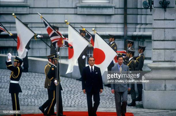 Charles Prince of Wales inspects a guard of honour at the Akasaka Palace Tokyo Japan Accompanied by Mr Yasuhiro Nakasone and behind is his equerry...