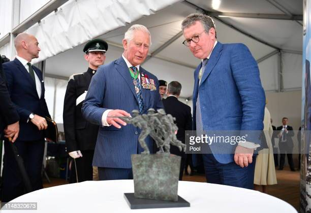 Charles Prince of Wales looks at a new Normandy sculpture after the the Royal British Legion Service of Remembrance at the Commonwealth War Graves...