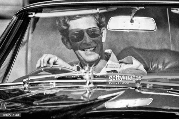 Charles, Prince of Wales pictured wearing sunglasses, smiling at the wheel of his Aston Martin sports car at the Windsor, England polo grounds.(Photo...