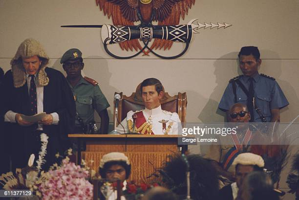 Charles, Prince of Wales, represents the Queen at the independence celebrations in Papua New Guinea, September 1975. Above his head, the National...