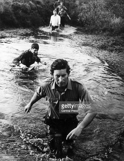 Charles, Prince of Wales, wading through a river.