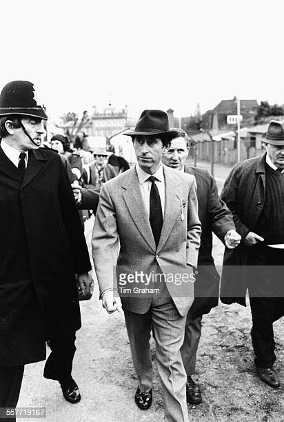 Charles Prince of Wales wearing a hat and tweed suit as he walks with a policeman circa 1985