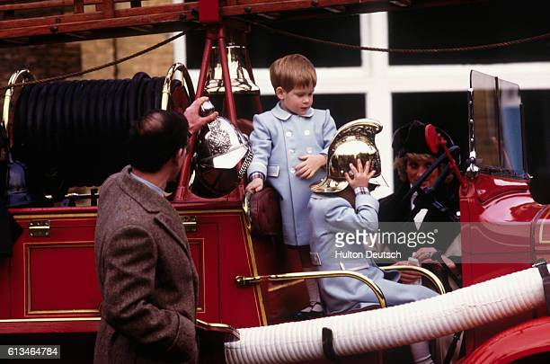 Charles Prince of Wales with his sons Prince Harry and Prince William who are playing on a vintage fire engine and his wife Princess Diana at...
