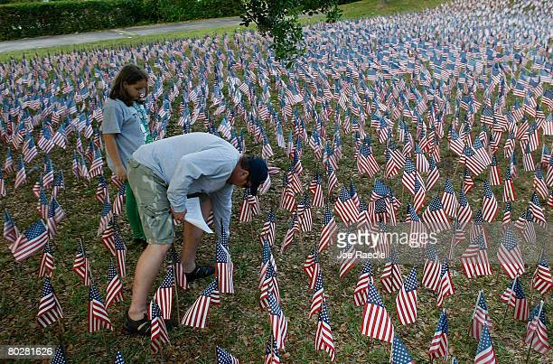 Charles Seilkop and Micayla Seilkop fix some of the blown over American flags that represent the 4454 American soldiers killed in the Iraq and...