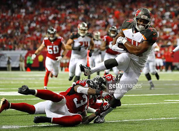 Charles Sims of the Tampa Bay Buccaneers rushes for a touchdown after breaking a tackle by Ricardo Allen of the Atlanta Falcons at Georgia Dome on...