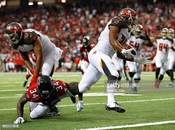 Charles Sims of the Tampa Bay Buccaneers rushes for a touchdown after breaking a tackle by Brian Poole of the Atlanta Falcons at Georgia Dome on...