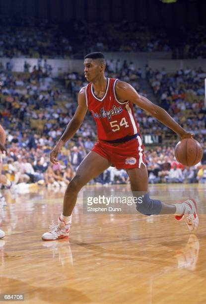 Charles Smith of the Los Angeles Clippers dribbles the ball during the NBA game against the Los Angeles Lakers at the Great Western Forum in Los...