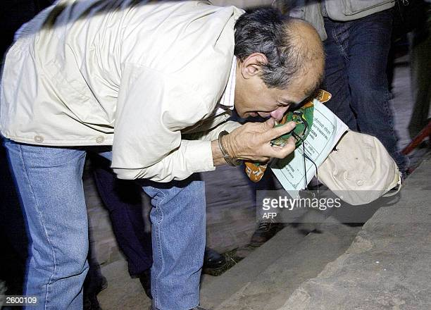 Charles Sobhraj attempts to retrieve his glasses, hat and handkerchief as he leaves court in Kathmandu, 15 October 2003. Convicted criminal Charles...