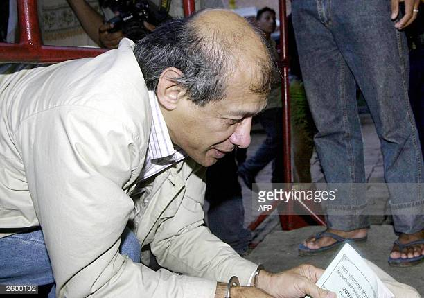 Charles Sobhraj bends down to retreive his hat and handkerchief in Kathmandu, 15 October 2003. Convicted criminal Sobhraj was produced in a Nepalese...