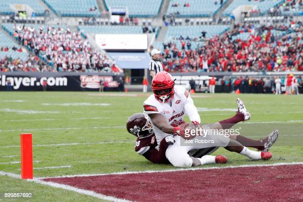 Charles Standberry of the Louisville Cardinals reaches for the end zone for a fiveyard touchdown reception in the first quarter of the TaxSlayer Bowl...