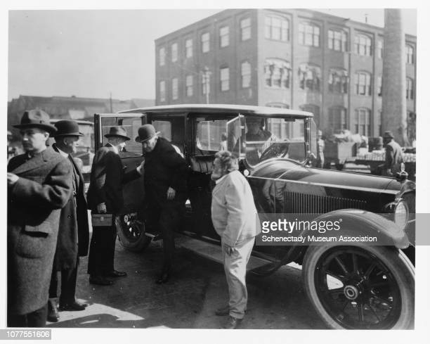 Charles Steinmetz waits as Thomas Edison exits a vehicle during Edison's visit to General Electric's Schenectady plant