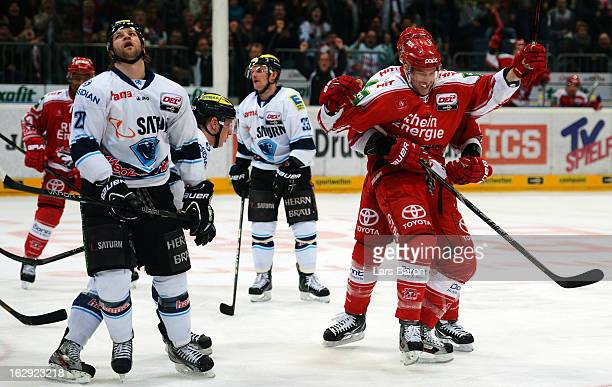 Charles Stephens of Koeln celebrates with team mate John Tripp next to Craig Weller of Ingolstadt after scoring his teams second goal during the DEL...
