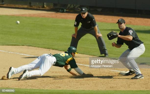 Charles Thomas of the Oakland Athletics slides safely past first baseman Conor Jackson of the Arizona Diamondbacks during the MLB spring training...