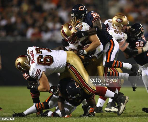 Charles Tillman of the Chicago Bears leaps to tackle Zak Keasey of the San Francisco 49ers as Lance Briggs of the Bears blocks Alan Reuber of the...