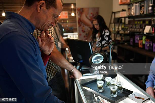 Charles Tilmore of Puerto Rico asking questions and looking over the stock on the shelves at Simply Pure's dispensary in Denver as part of a visit to...
