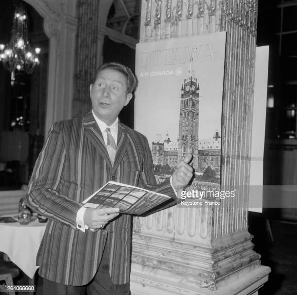 Charles Trenet devant une affiche d'Ottawa avant son départ pour le Canada dans un grand hôtel parisien le 3 avril 1966 à Paris, France.