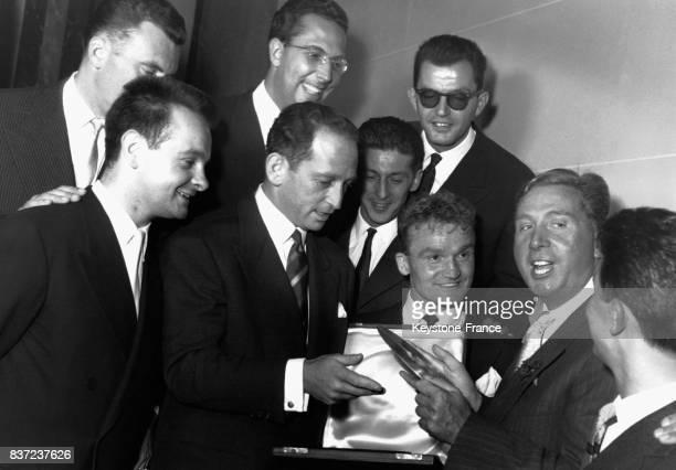 Charles Trénet remet à JeanLouis Joubert le directeur artistique des Compagnons de la chanson le disque d'or pour avoir vendu un million d'albums à...