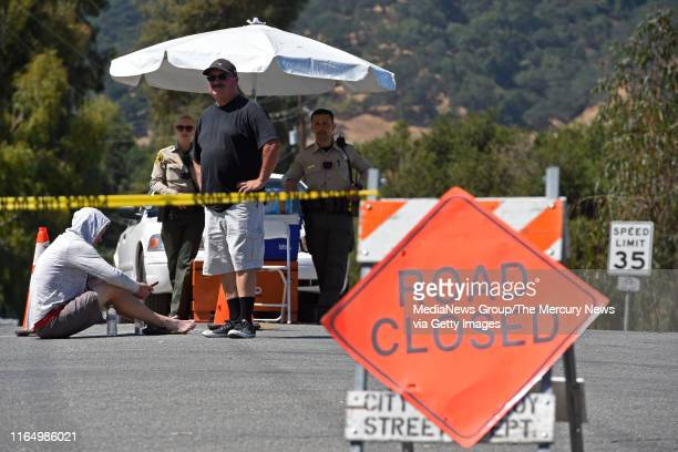 Charles Trujillo, of Gilroy, stands by a police checkpoint at the corner of Uvas Park Drive and Miller Avenue as police stand guard at the entrance...