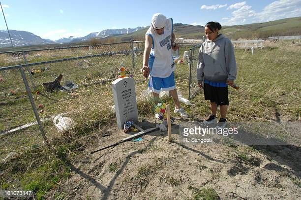 BROWNING MONTANA Charles Wells left pours his buried grandfather a shot of vodka as Wells' friend Shannon Lamott watches the liquid hit the grave The...