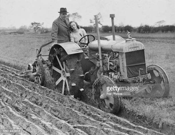 Charles Wilcock a former Royal Navy officer instructs Miss Duckworth, a recruit for the Women's Land Army on operating a Standard Fordson tractor...