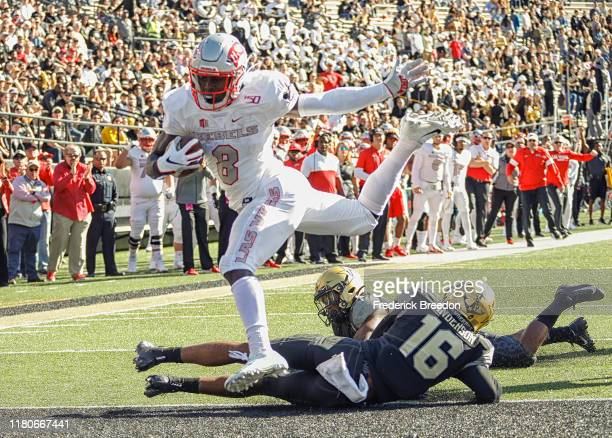 Charles Williams of the UNLV Rebels is tripped up by BJ Anderson of the Vanderbilt Commodores as he goes into the end zone for a touchdown during the...