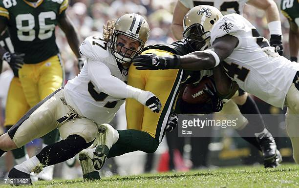 Charles Woodson of the Green Bay Packers is tackled by Steve Gleason and Danny Clark of the New Orleans Saints on September 17 2006 at Lambeau Field...