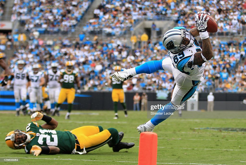 Charles Woodson #21 of the Green Bay Packers watches as Steve Smith #89 of the Carolina Panthers dives for a ball during their game at Bank of America Stadium on September 18, 2011 in Charlotte, North Carolina.