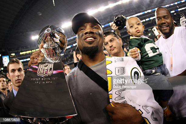 Charles Woodson of the Green Bay Packers, who was injured during the game, celebrates with the Vince Lombardi Trophy after they defeated the...