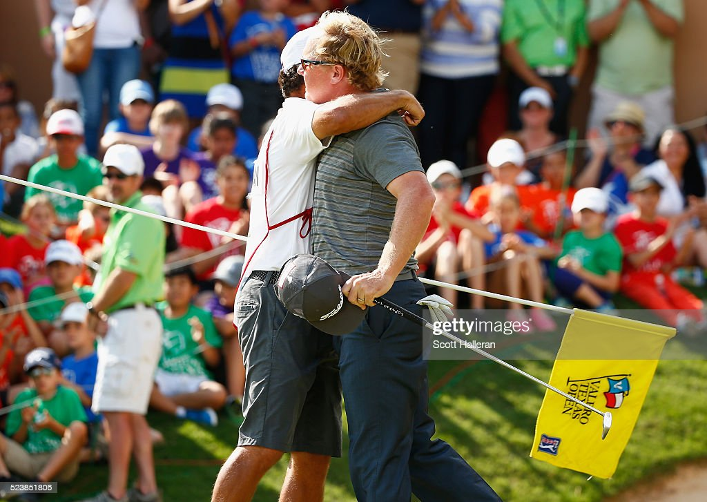 Charley Hoffman celebrates with his caddie Brett Waldman after putting on the 18th hole during the final round of the Valero Texas Open at TPC San Antonio AT&T Oaks Course on April 24, 2016 in San Antonio, Texas.