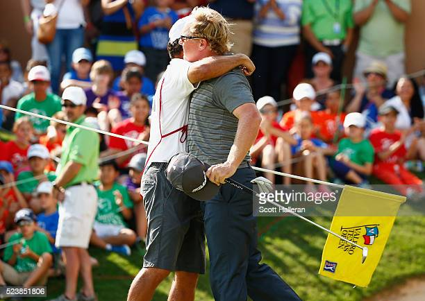 Charley Hoffman celebrates with his caddie Brett Waldman after putting on the 18th hole during the final round of the Valero Texas Open at TPC San...
