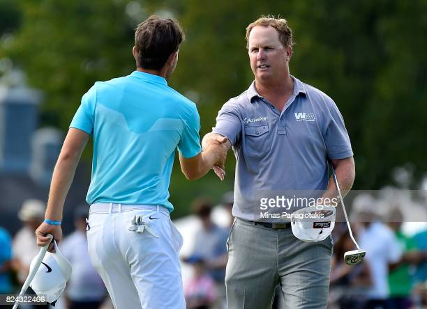 Charley Hoffman of the United States shakes hands with Ryan Ruffels of Australia on the 18th green during the third round of the RBC Canadian Open at...