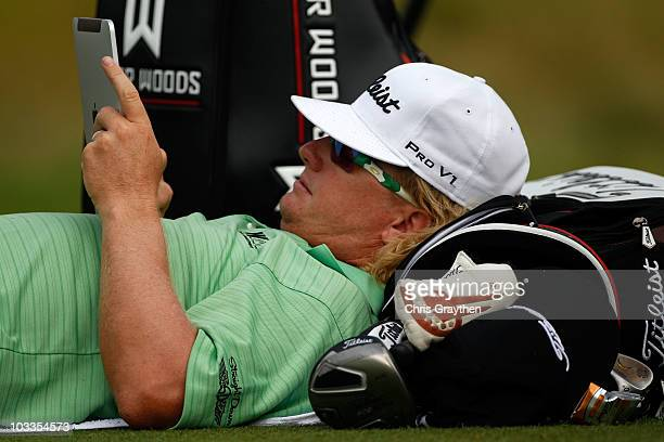 Charley Hoffman uses his iPad during a weather delay prior to the start of the first round of the 92nd PGA Championship on the Straits Course at...