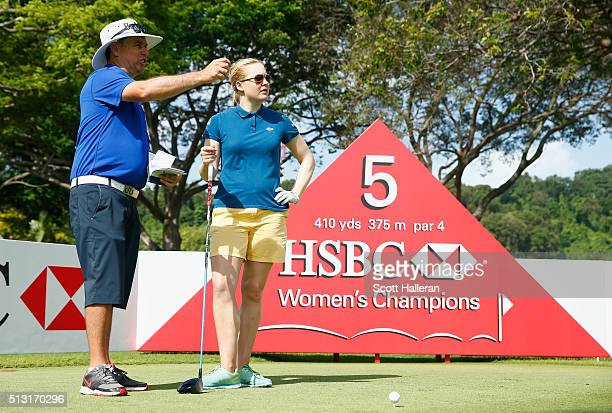 Charley Hull of England lines up a shot with her caddie Adam Woodward during a practice round prior to the start of the HSBC Women's Champions at...