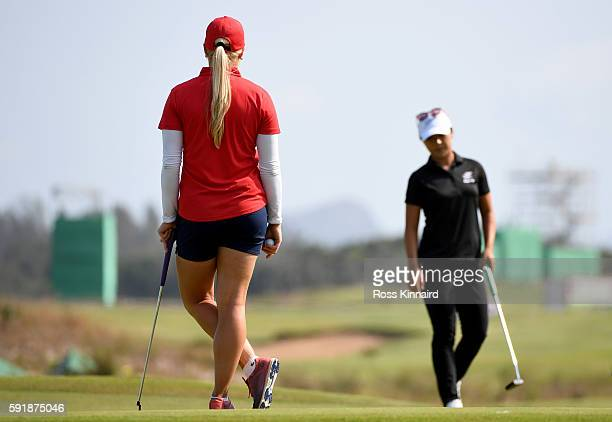 Charley Hull of Great Britain watches Lydia Ko of New Zealand on the 18th green during the second round of the Women's Individual Stroke Play golf on...