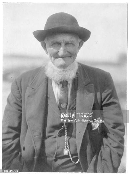 Charley Sennett with hat and white beard dressed in threepiece suit with tie pocket watch and handkerchief in breast pocket Bailey Island Maine 1908