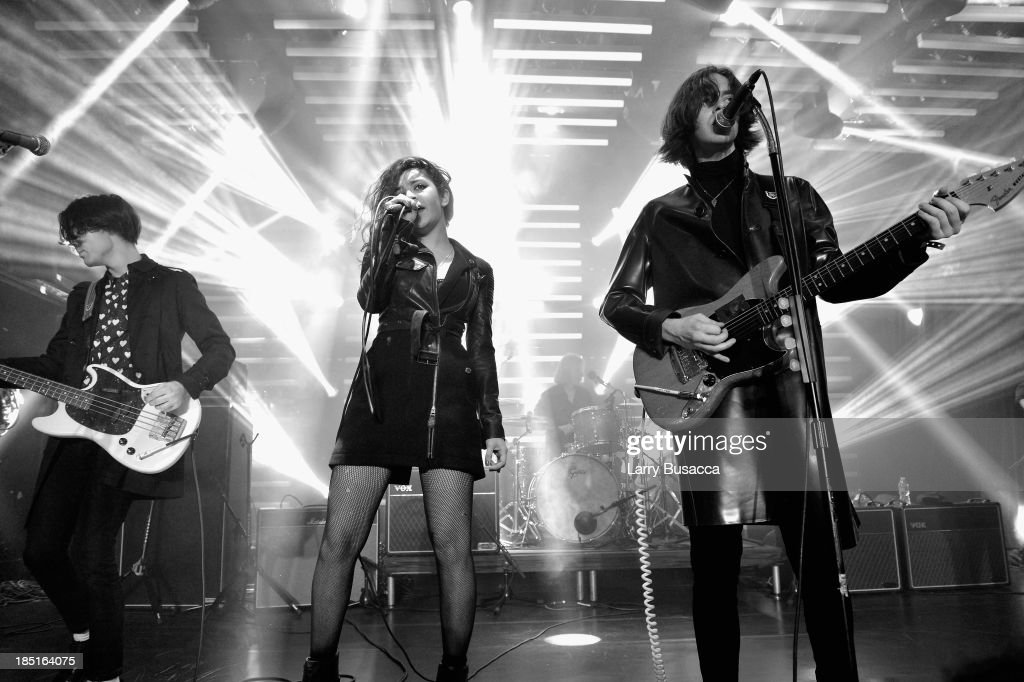 Charli XCX (C) with Samuel Koisser (L) and Harry Koisser (R) of the band Peace perform at the Burberry Brit Rhythm Men's Launch in New York at Irving Plaza on October 17, 2013 in New York City.