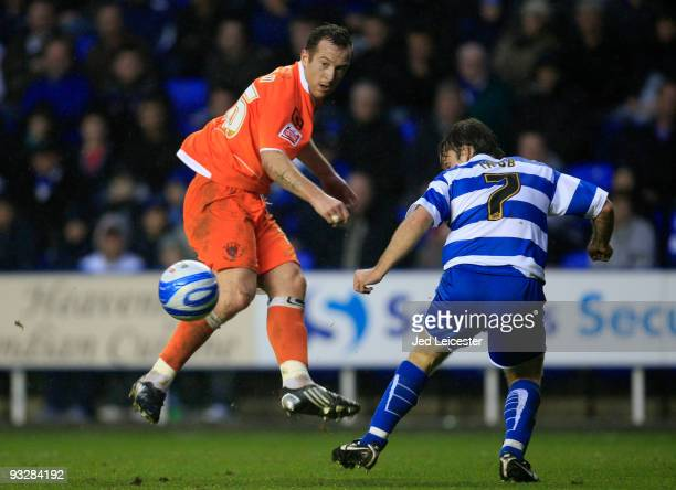 Charlie Adam of Blackpool chips the ball past Jay Tabb of Reading during the Coca Cola Championship match between Reading and Blackpool at the...