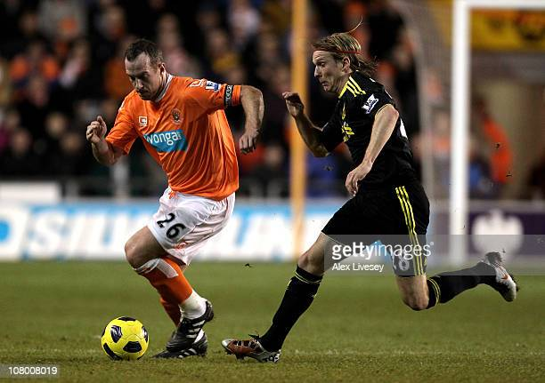 Charlie Adam of Blackpool is pursued by Christian Poulsen of Liverpool during the Barclays Premier League match between Blackpool and Liverpool at...