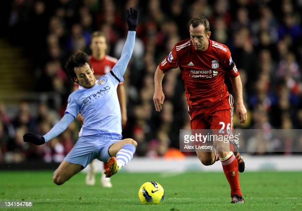 Charlie Adam of Liverpool is challenged by David Silva of Manchester City during the Barclays Premier League match between Liverpool and Manchester...