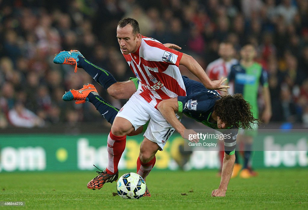 Charlie Adam of Stoke City battles for the ball with Fabricio Coloccini of Newcastle United during the Barclays Premier League match between Stoke City and Newcastle United at Britannia Stadium on September 29, 2014 in Stoke on Trent, England.
