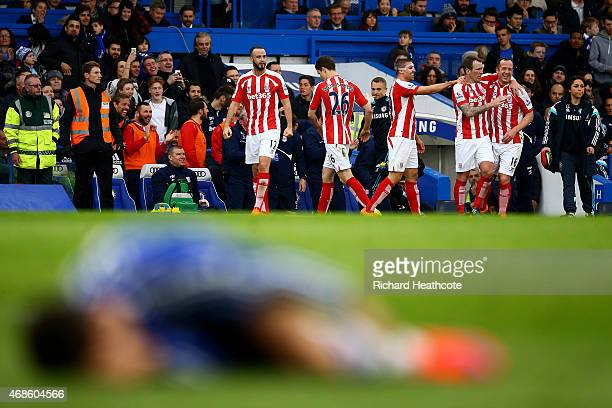 Charlie Adam of Stoke City celebrates with teammates after scoring his team's first goal as Eden Hazard of Chelsea lies on the floor during the...