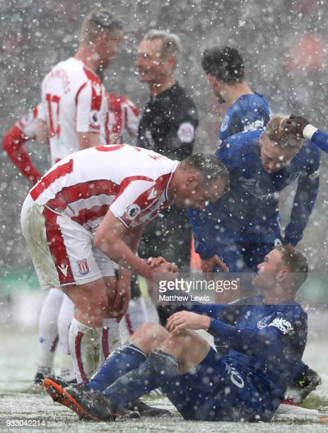 Charlie Adam of Stoke City checks if Wayne Rooney of Everton is ok during the Premier League match between Stoke City and Everton at Bet365 Stadium...