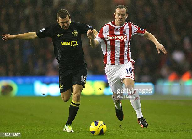 Charlie Adam of Stoke City holds off a challenge from James McArthur of Wigan Athletic during the Barclays Premier League match between Stoke City...