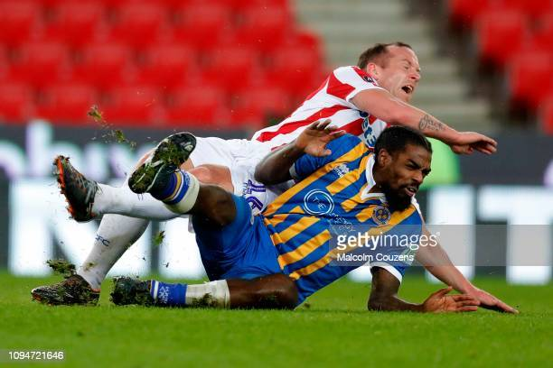 Charlie Adam of Stoke City is tackled by Anthony Grant of Shrewsbury Town during the FA Cup Third Round Replay match between Stoke City and...