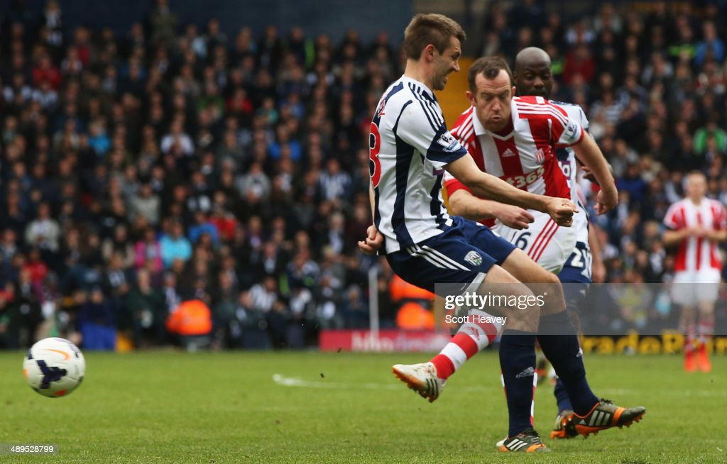 Charlie Adam of Stoke City shoots past Gareth McAuley of West Bromwich Albion as he scores their second goal during the Barclays Premier League match between West Bromwich Albion and Stoke City at The Hawthorns on May 11, 2014 in West Bromwich, England.