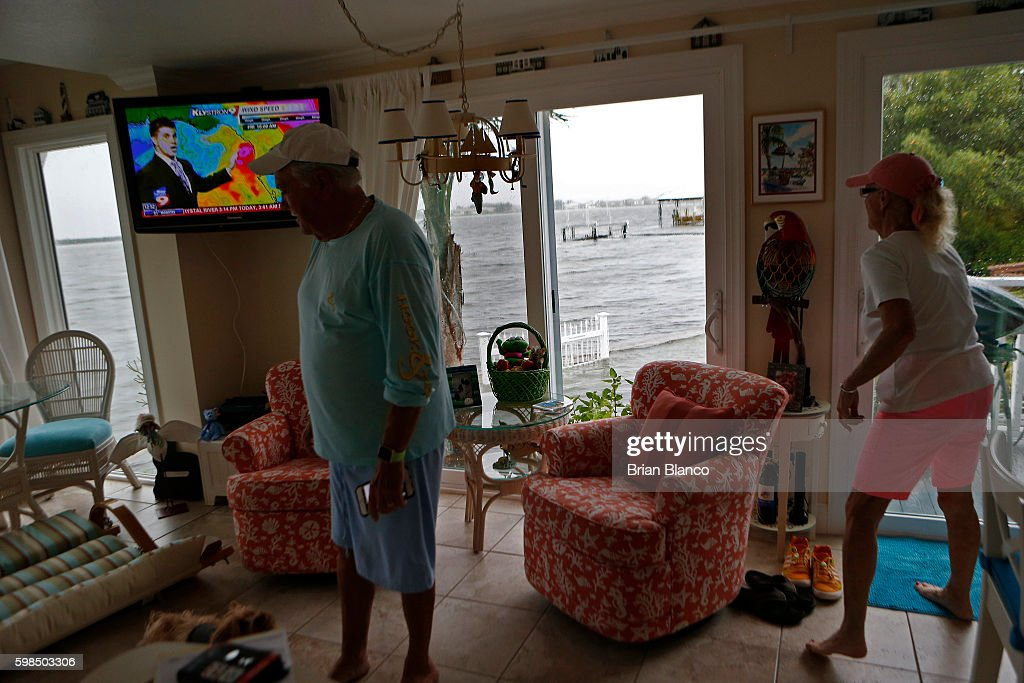 Charlie and Brenda Miller watch an update on the weather as they monitor the seawall outside their home at the Sandpiper Resort as rising water comes from the Gulf of Mexico into their front yard as winds and storm surge associated with Tropical Storm Hermine impact the area on September 1, 2016 at in Holmes Beach, Florida. Hurricane warnings have been issued for parts of Florida's Gulf Coast as Hermine is expected to make landfall as a Category 1 hurricane