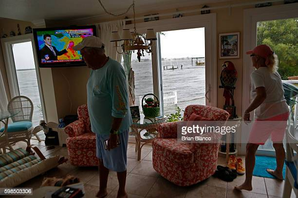 Charlie and Brenda Miller watch an update on the weather as they monitor the seawall outside their home at the Sandpiper Resort as rising water comes...