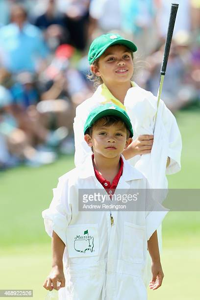 Charlie and Sam Woods works as a caddies for their father Tiger Woods during the Par 3 Contest prior to the start of the 2015 Masters Tournament at...