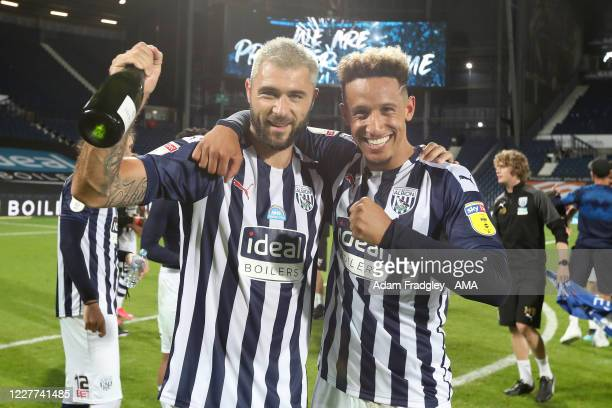 Charlie Austin and Callum Robinson of West Bromwich Albion celebrate promotion to the Premier League on the pitch at the end of the Sky Bet...