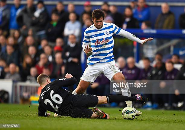 Charlie Austin of QPR is tackled by John Stones of Everton during the Barclays Premier League match between Queens Park Rangers and Everton at Loftus...